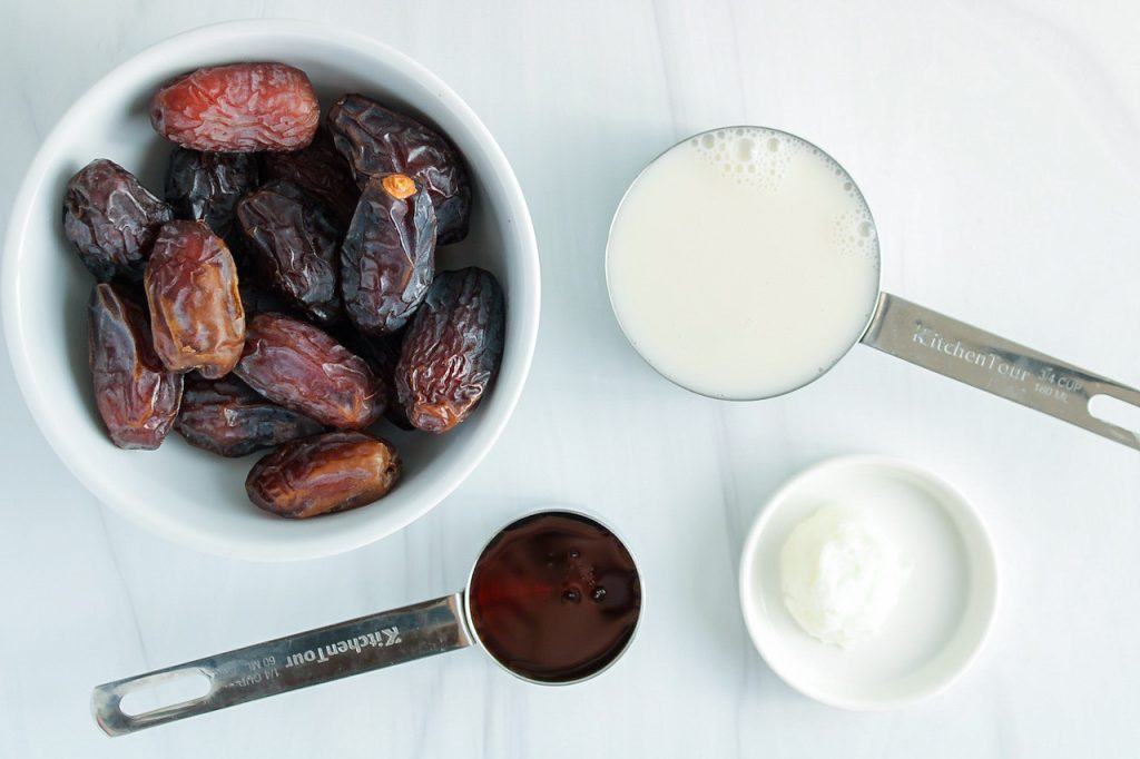 Showing are the ingredients needed to make this recipe: fresh medjool dates, maple syrup, coconut oil and vegan milk