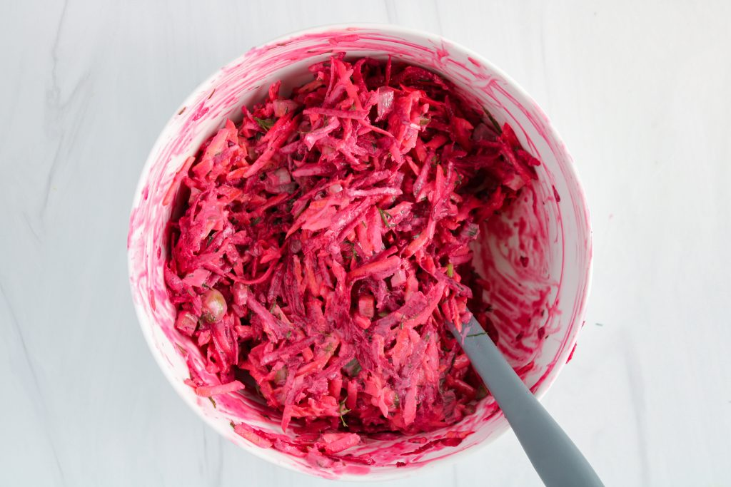 There is a large white bowl with a bright pink beet mixture that was stirred using a grey spatula.