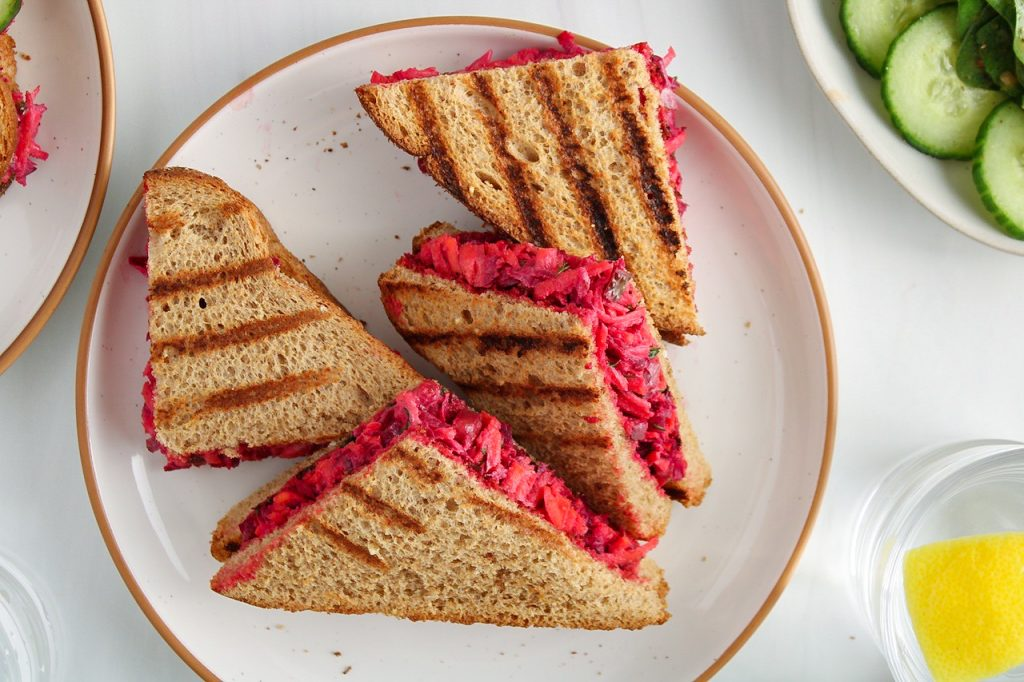 There is a beetroot and pickle sandwich that's cut in a triangle shape on a white plate. There is a green salad with cucumber on the side.