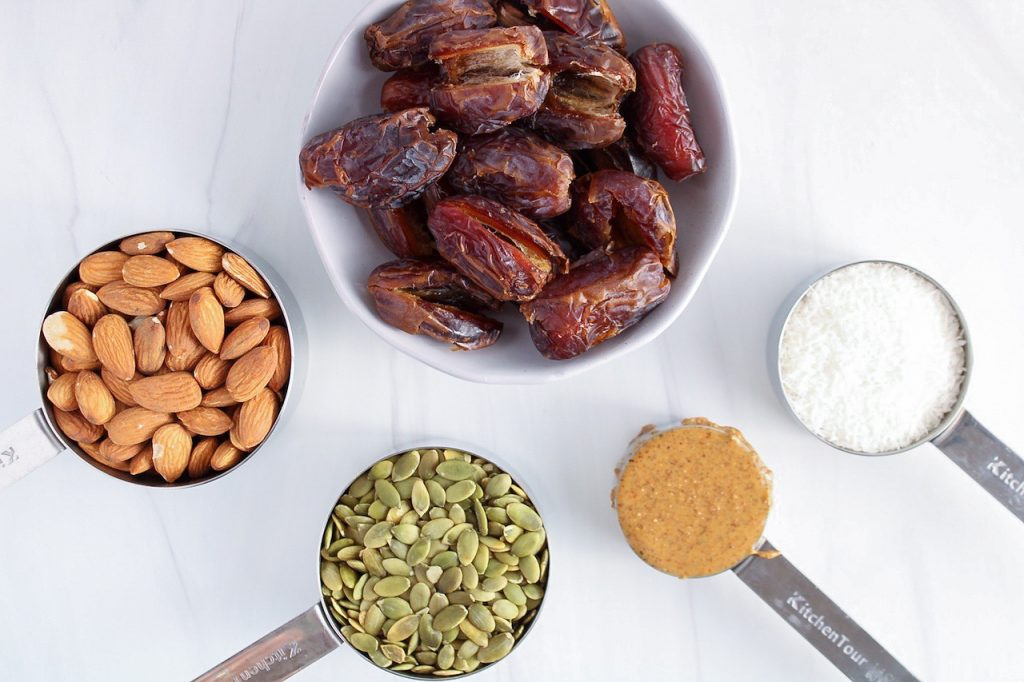 Ingredients needed to make the crust: medjool dates, almond butter, shredded coconut, raw pumpkin seeds, almonds.