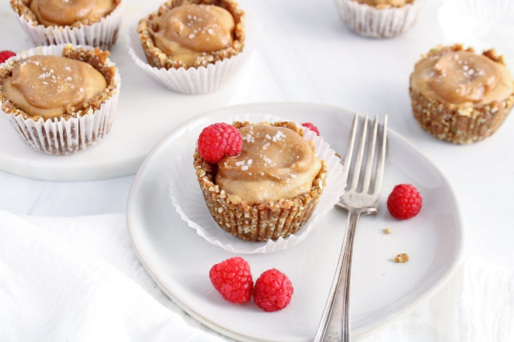 Showing is a vegan caramel ice cream cup on a plate with raspberries on the side and a fork. There are more cups in the background.