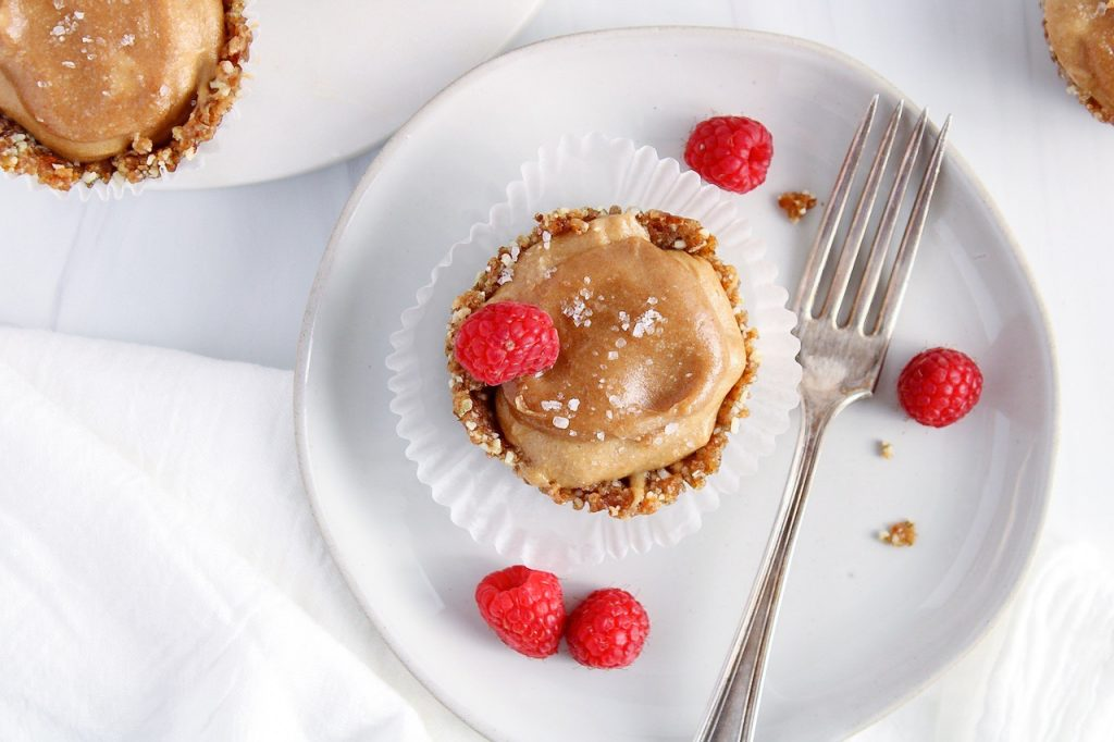 Showing is a vegan caramel ice cream cup on a plate with raspberries on the side and a fork. There are more cups on the table on the side.