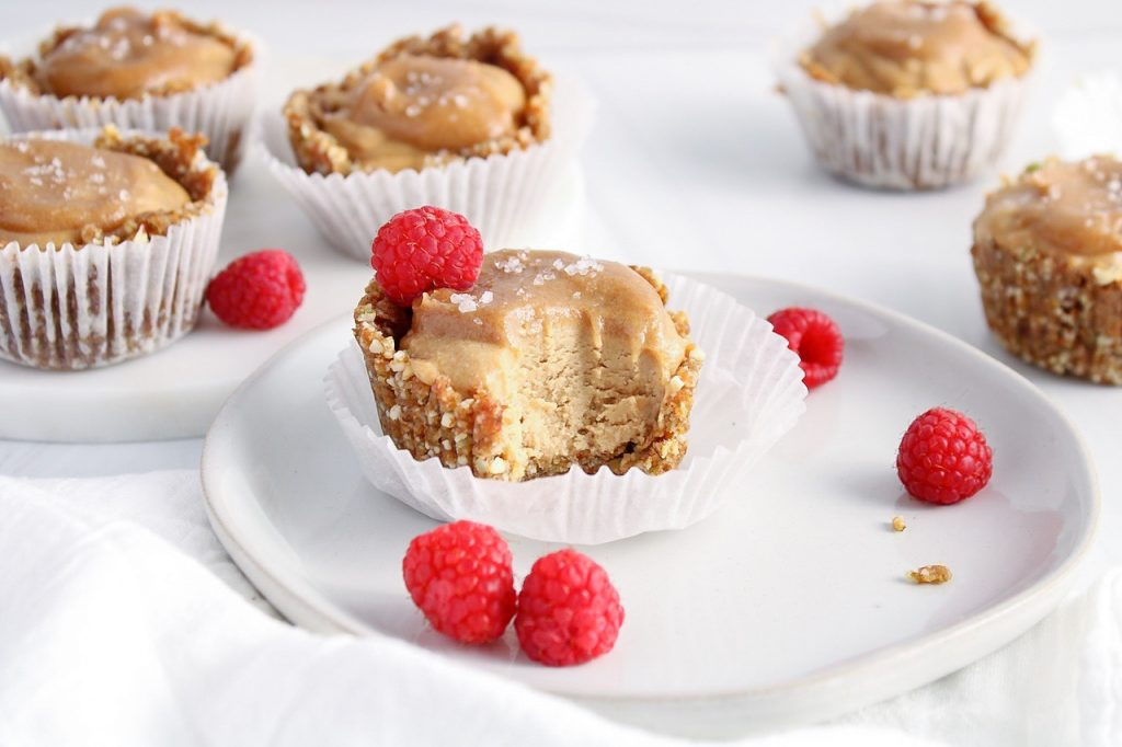 Showing is a caramel ice cream cup on a plate with a bite taken off to show the texture. There are fresh raspberries on the side on the plate. You can see more ice cream cup in the background.