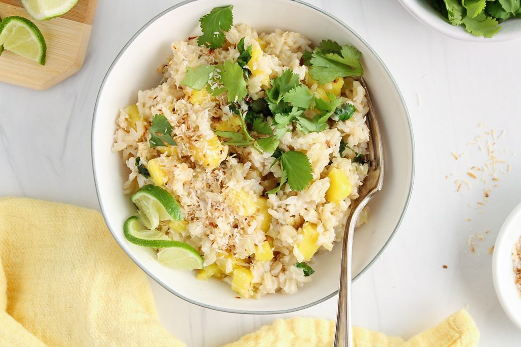 There is a white bowl containing a coconut pineapple rice that's topped with fresh cilantro, toasted shredded coconut and a lime wedge. There are more coconut, cilantro and lime on the side as well as a yellow hand towel.