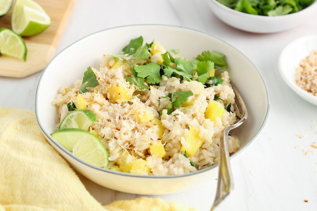 There is a coconut pineapple rice in a small white bowl that's topped with shredded coconut and lime wedges. There are more of the toppings in bowls around the dish. There is a fork on the side of the bowl.