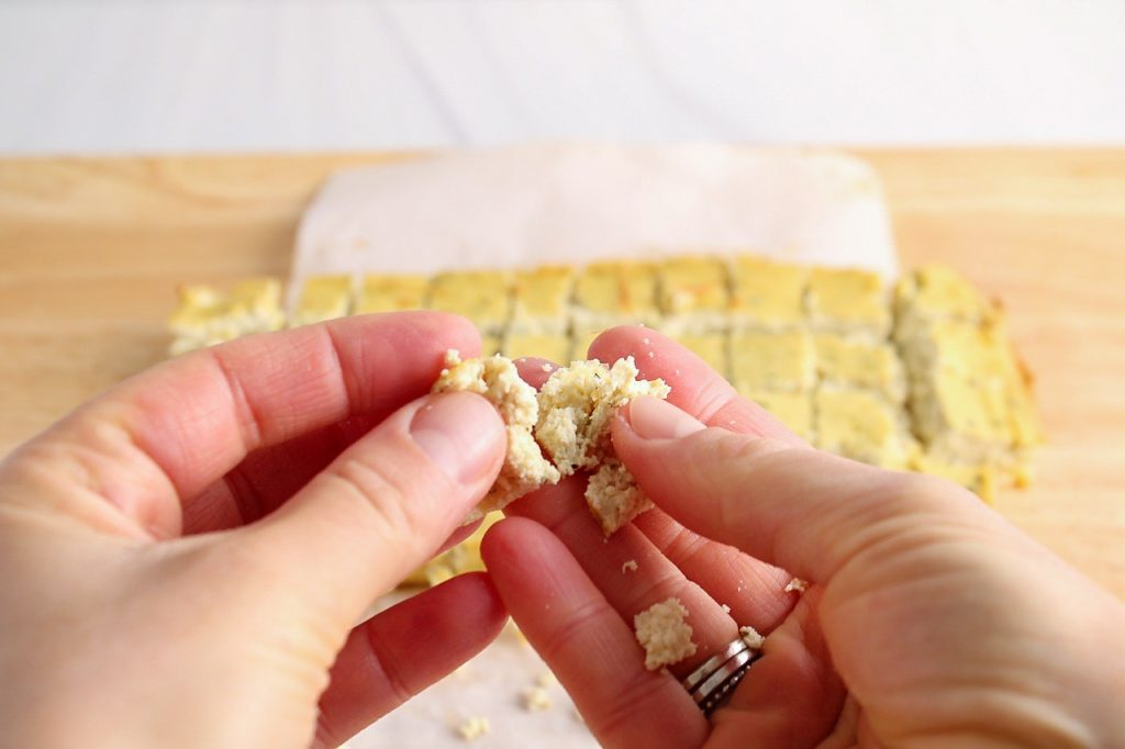 Close up on 2 hands holding on a cube of oven-baked tofu mixture to show its crumbly texture.