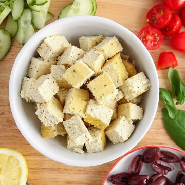 Overhead view on a white bowl containing cubes of vegan feta cheese. There are chopped cherry tomatoes, kalamata olives, cucumbers and red onion on the side as well as half of a lemon and a black and white hand towel.