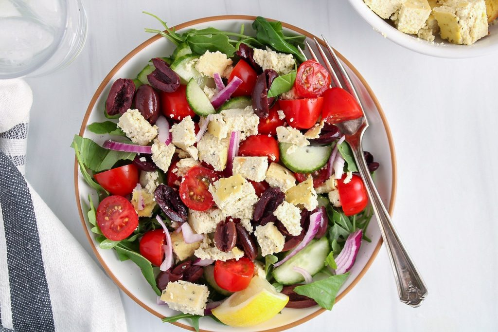 Showing is a white plate containing a arugula salad filled with kalamata olives, sliced cucumbers, cherry tomatoes, sliced red onion and cubed vegan feta cheese.