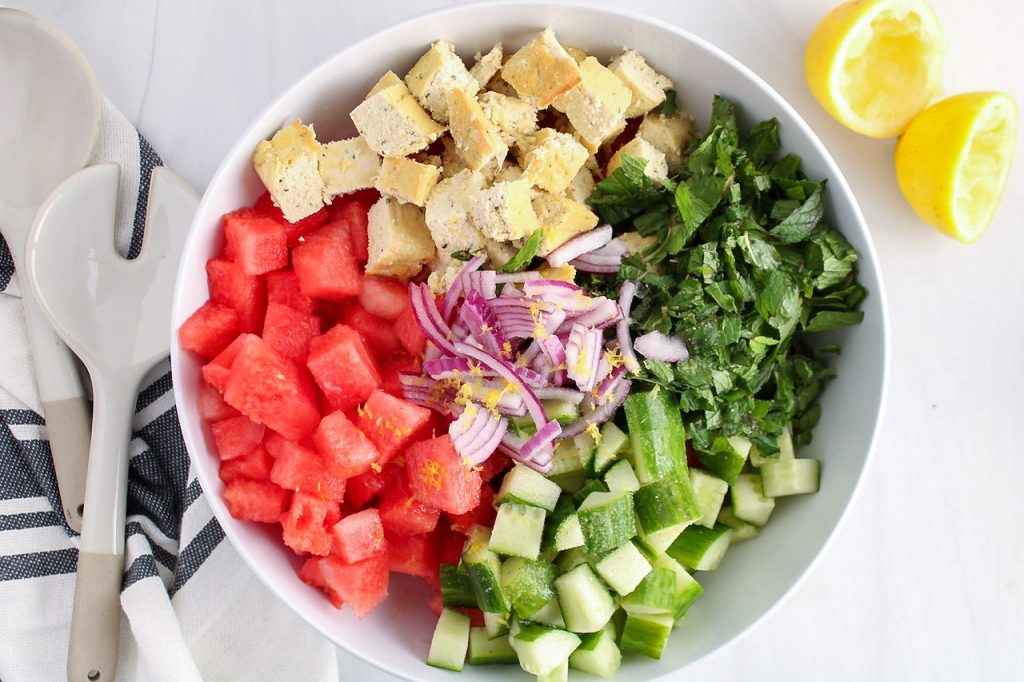 Showing is a large white bowl containing the ingredients to make this recipe: watermelon, cucumber, red onion, mint, lemon zest and cubed homemade vegan feta cheese.