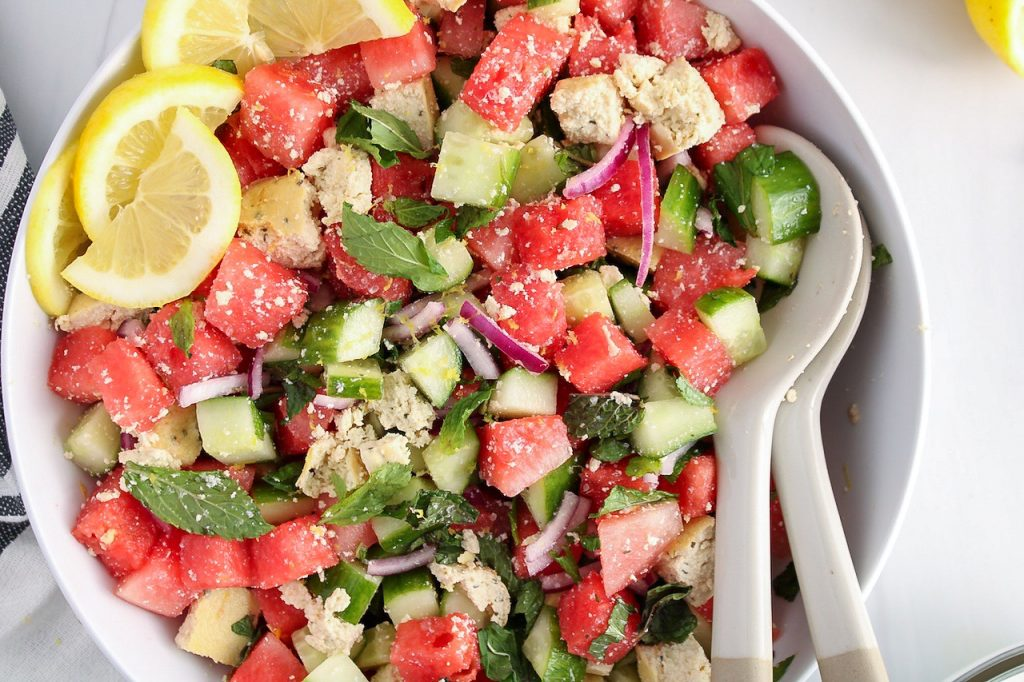 There is a vegan watermelon salad in a large white bowl with a side of sliced lemon and 2 large mixing spoons.