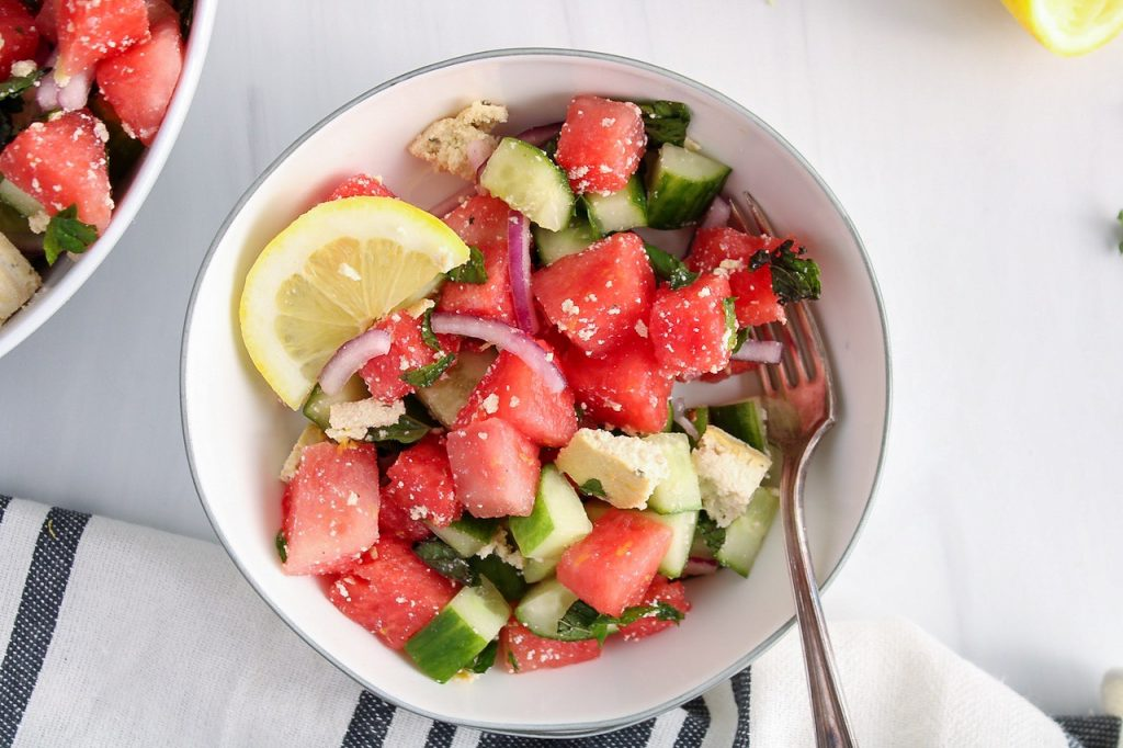 There is a vegan watermelon salad in a small white bowl with a side of lemon wedge and a fork in the bowl. There is a white and black hand towel on the side as well as a large bowl containing more of the salad.