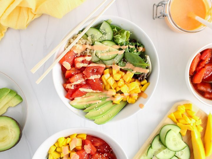 There is a white bowl containing a quinoa poke bowl made with tomato tuna. The bowl is also garnished with diced tomatoes, sliced cucumber and avocado and there is so green lettuce on the side of the bowl. On the table around the poke bowl, there are more of the garnishes in bowls.