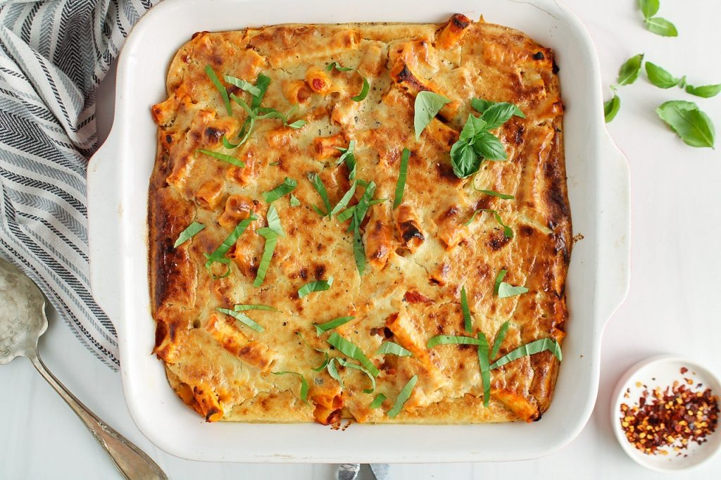 Showing is a large square dish containing a vegan baked ziti filled with lentils and topped with fresh basil. There are a serving spoon, more fresh basil, red pepper flakes and a hand towel on the side of the baking dish.