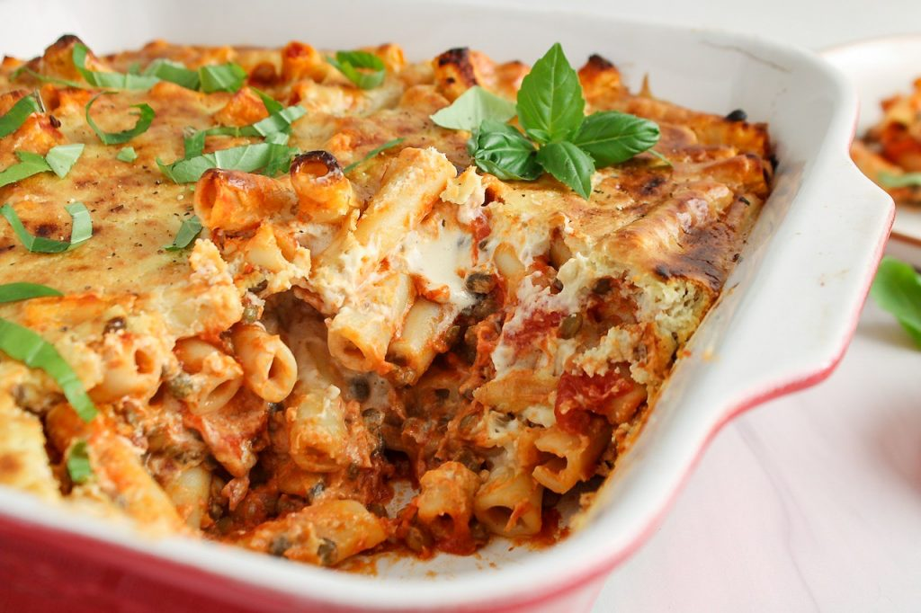 Close up on a vegan baked ziti dish that's still in its baking dish with a portion that was remove to show its interior texture. You can see pockets of creamy cashew cream mixed in with the marinara sauce.