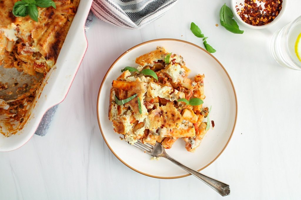 Showing is a portion of a vegan baked ziti that's on a plate and topped with fresh basil with a fork on the side of the plate. There is athe baking dish containing the pasta dish on the side of the plate and there are red pepper flakes, fresh basil, a hand towel and a glass of water on the side as well.