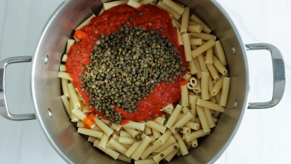 There are cooked ziti noodles in a large pot topped with a marinara sauce and cooked lentils.