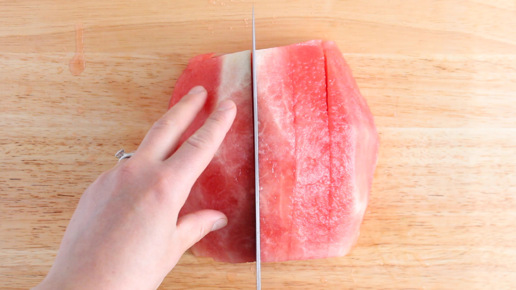 Showing is the technique on how to dice a watermelon. You can see half of a watermelon on a wooden cutting board with a knife cutting it in the shape of long sticks.