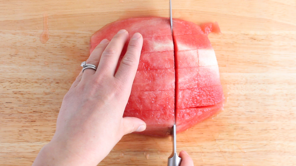 Showing is the technique on how to dice a watermelon. You can see half of a watermelon on a wooden cutting board with a knife cutting it in the shape of cubes.