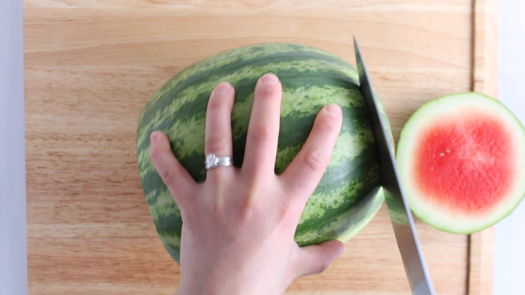 Showing is the technique on how to dice a watermelon. You can see a knife cutting the edge of both side of a large watermelon.