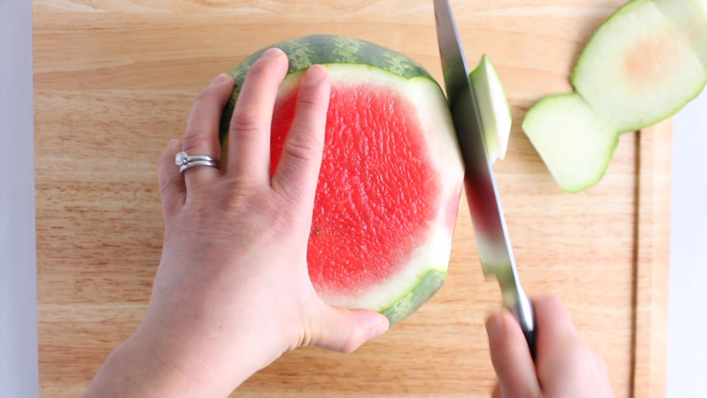 Showing is the technique on how to dice a watermelon. Over head view: You can see a knife cutting off the peel of a large watermelon.