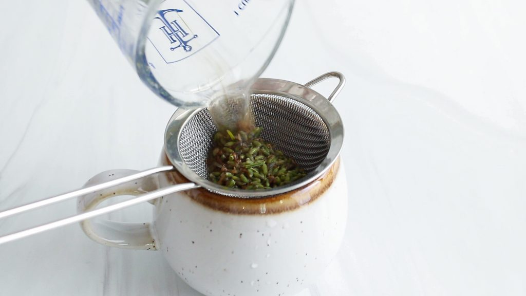 You can see a cup pouring a lavender tea over a small colander to strain the tea.