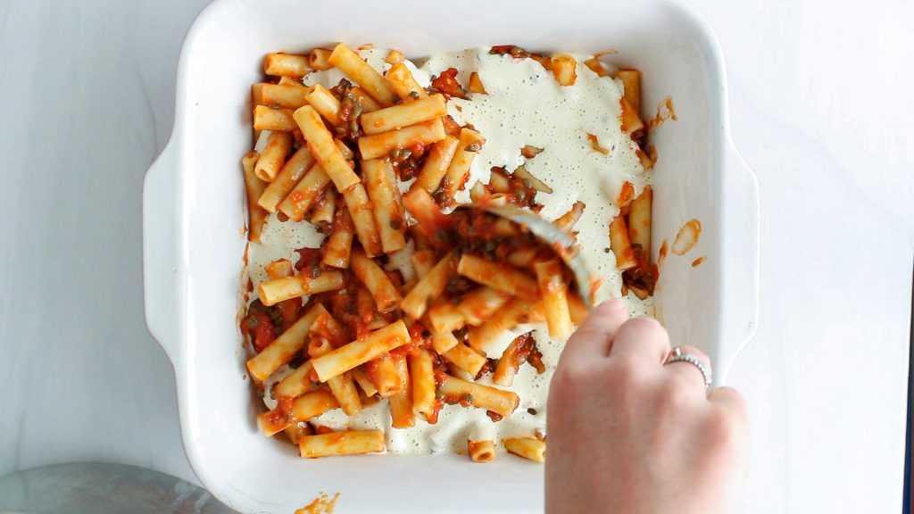 There is a mixture of noodle with a tomato sauce that's topped with a creamy white sauce in a large baking dish. You can see a hand adding more of the noodles over the dish.