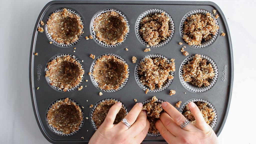 You can see 2 hands molding a soft crumbly mixture into a muffin mold