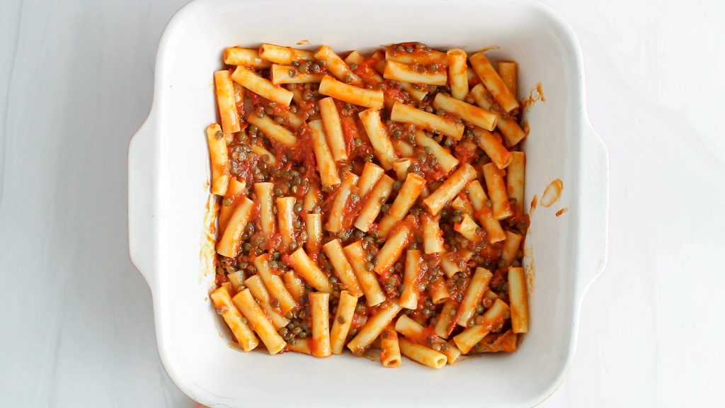 Showing are noodles tossed in a tomato sauce and placed in a large square baking dish.