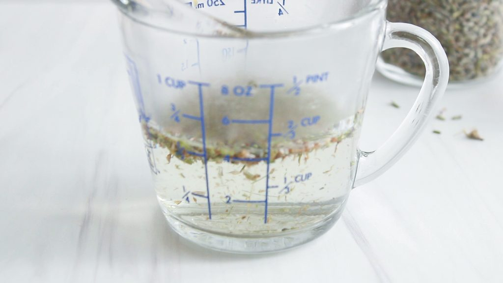 Close up on a measuring cup that contains hot water with lavender flower (steeping the tea)