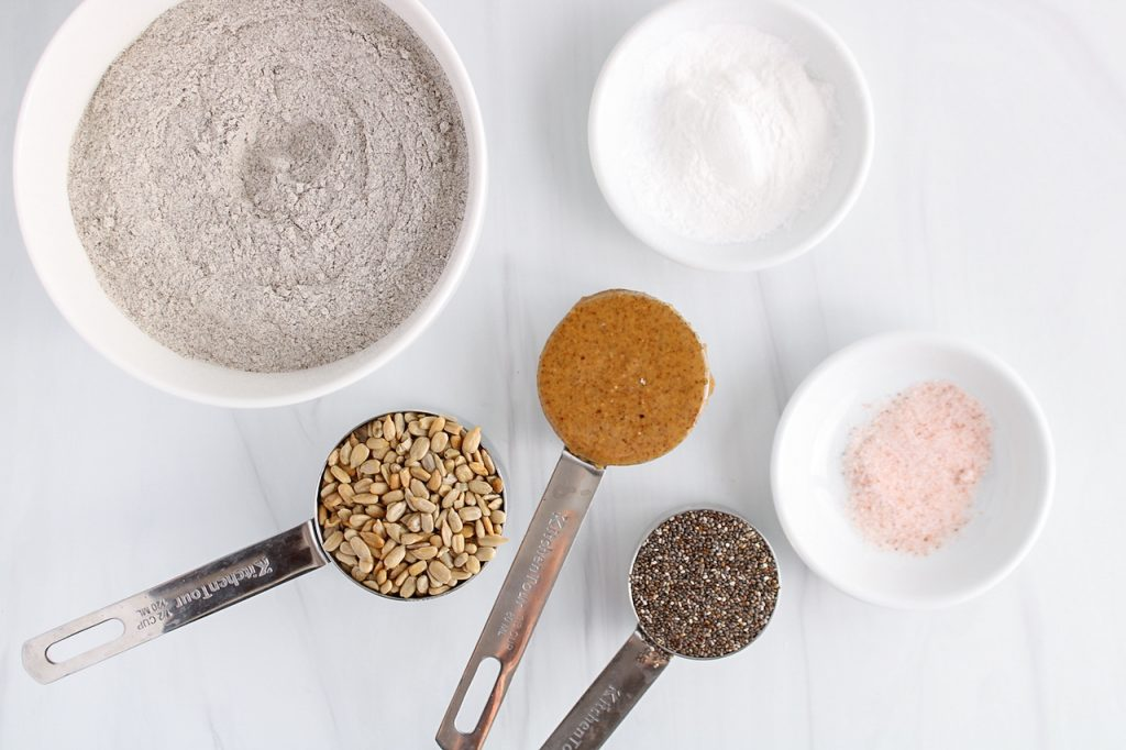 Showing are the ingredients needed to make this recipe: flour, salt, baking powder, chia seeds, sunflower seeds and almond butter