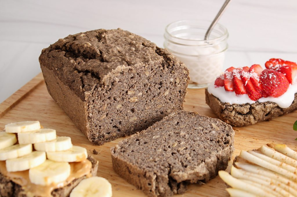 Showing is a homemade easy buckwheat bread that's about half sliced. There are a few slices around the bread that are topped with peanut butter, yogurt and fruits.