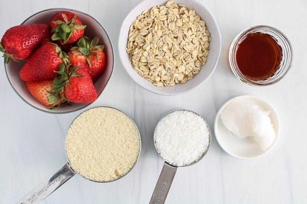 Showing are the ingredients needed to make the crust: strawberries, oats, maple syrup, almond flour, shredded coconut and coconut oil.