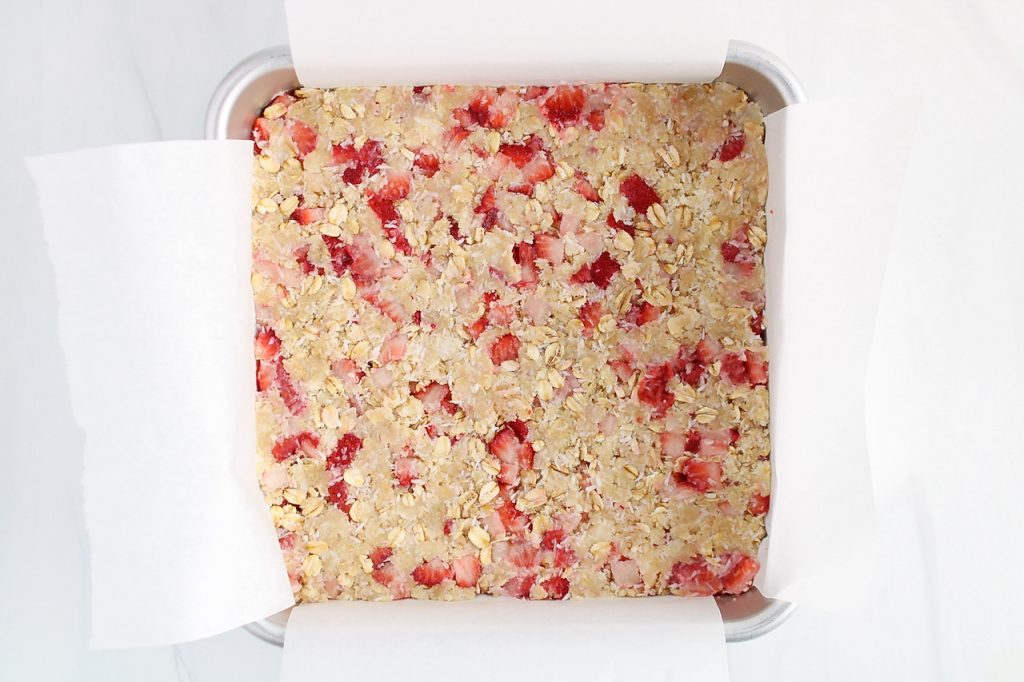 There is a oat-strawberry mixture in a square baking dish (crust of the bars)