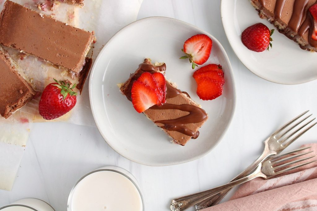 Overhead view on a strawberry chocolate bar that's on a plate and topped with a drizzle of melted chocolate and slices of strawberries.