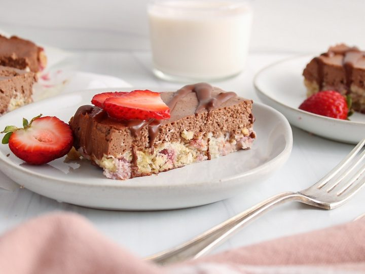 Showing is a strawberry chocolate bars that's on a plate and topped with fresh strawberries. There are more of the bars around and a fork on the side.