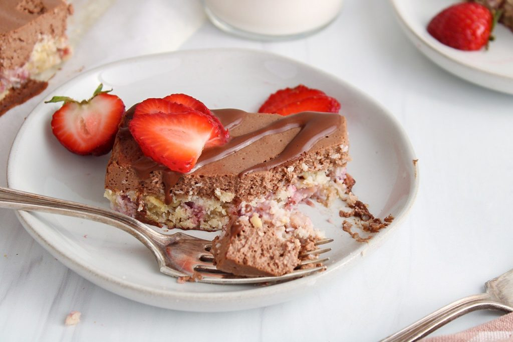 Showing is a strawberry chocolate bars that's on a plate and topped with fresh strawberries. There is a bite taken off from the bar with the fork holding on the bite on the side of the plate. There are more of the bars around and a fork on the side.