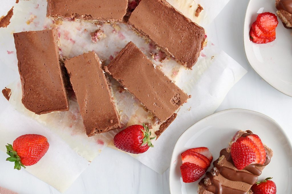 Showing are a few strawberry chocolate bars that are still on the parchment paper with fresh strawberries on the side. There 2 of the bars that are on plates.