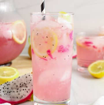 Close up on a tall glass filled with ice cubes and a homemade dragon fruit lemonade. You can see slices of lemon in the drink and there are more fruit as well as more lemonade in a large pitcher in the background
