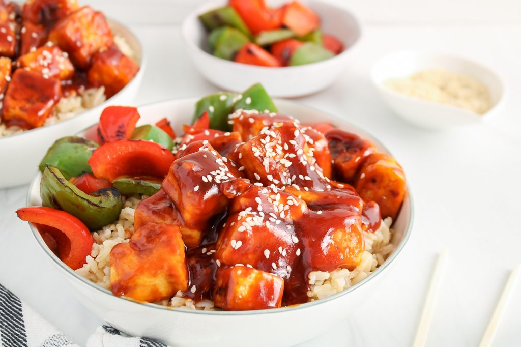 Close up on a dish containing brown rice that's topped with a sweet and sour tofu, red and green pepper and sprinkled with sesame seeds. There are bowl with more roasted peppers and sesame seeds in the back.