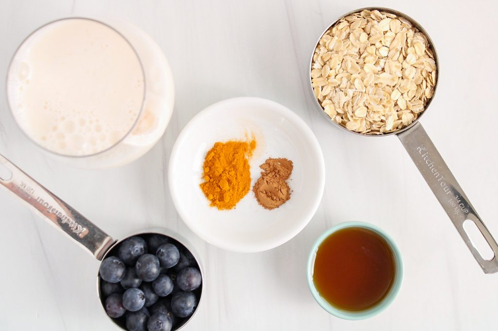 Showing are the ingredients needed to make this recipe: rolled oats, maple syrup, vegan milk, blueberries and spices.