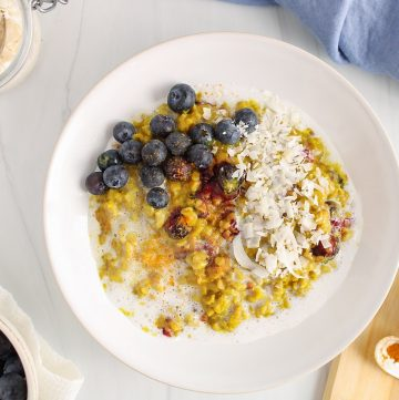 Overhead view on a white bowl containing a turmeric blueberry oatmeal that's topped with fresh blueberries and shredded coconut. Beside the bowl, there are a few bowls containing turmeric, fresh blueberries and shredded coconut.