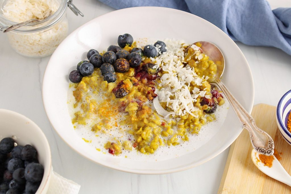 Front view on a white bowl containing a yellow turmeric oatmeal that's topped with fresh blueberries and shredded coconut. There is a spoon on the side of the bowl and more blueberries and coconut in small bowls on the side.
