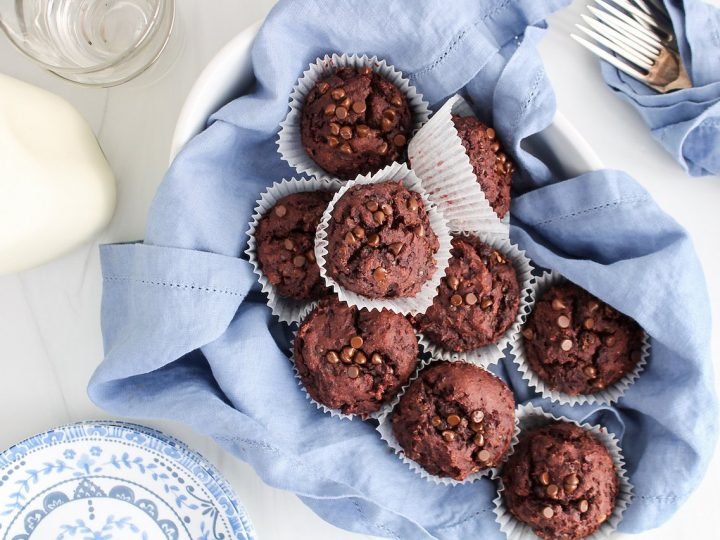 Showing are 9 beetroot chocolate muffins that are in a oval container that's covered with a blue hand towel. On the side, there are empty glasses, a jar with vegan milk, small white and blue plates and a few fork rolled in a blue hand towel.