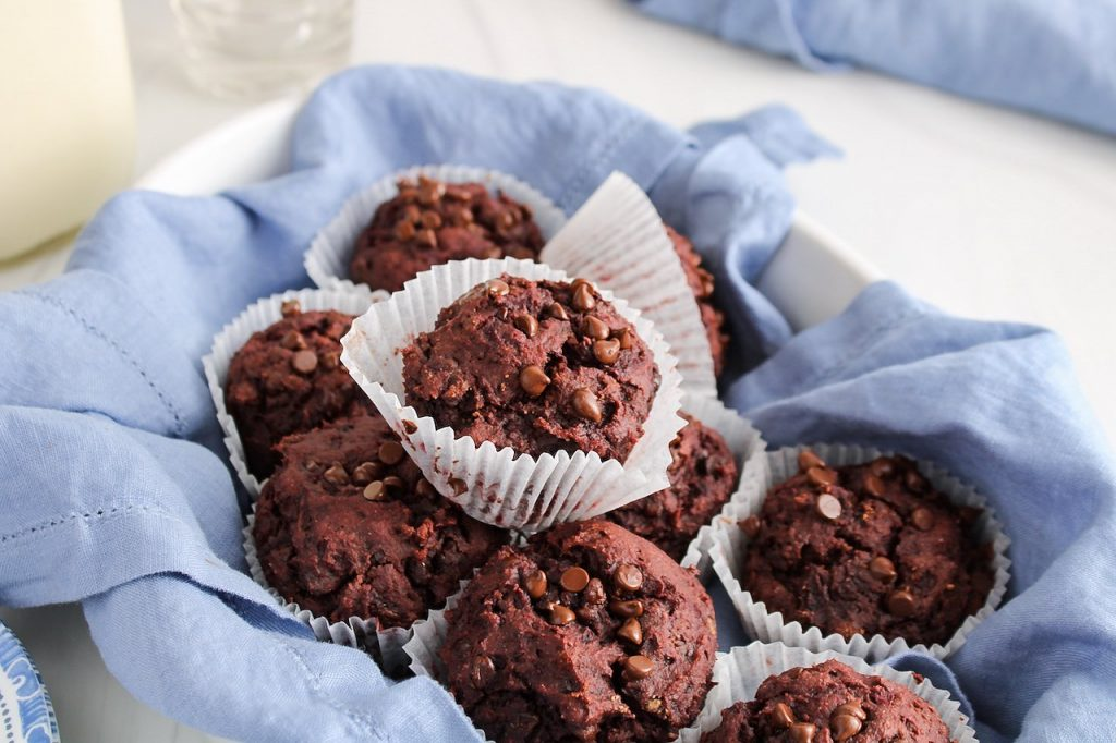 Front view of 9 beetroot chocolate muffins that are in a oval container that's covered with a blue hand towel. You can see empty glasses and a jar filled with vegan milk in the background.