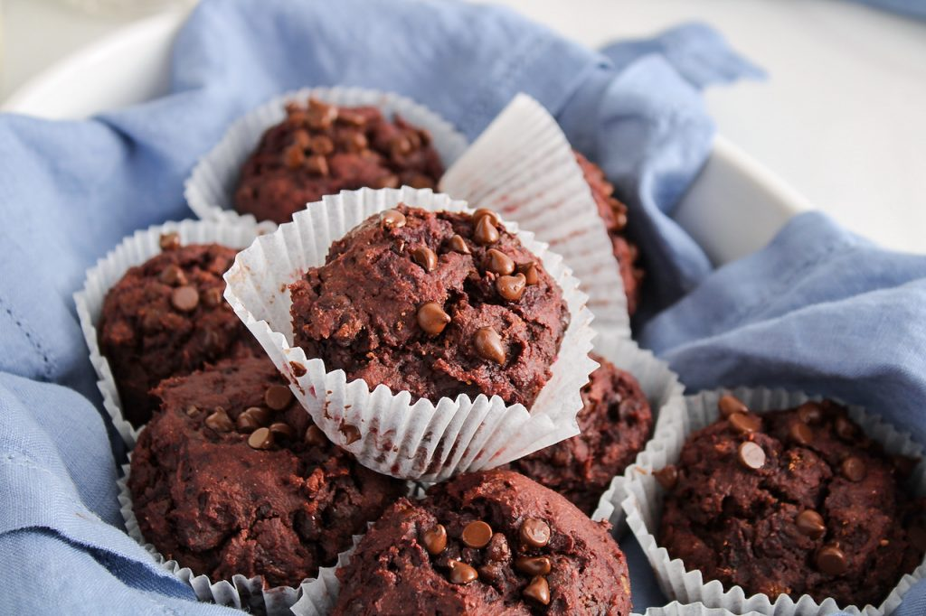 Close up on 9 beetroot chocolate muffins that are in a oval container that's covered with a blue hand towel.