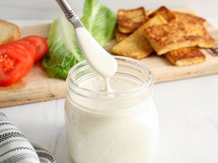 There is a jar that contains a quick cashew mayo with a butter knife taking some to show the texture. In the background, there are the fixings to make a sandwich: roasted tofu, sliced tomatoes, sliced bread and lettuce.