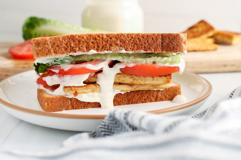 Showing is a sandwich that contains tofu, tomatoes, lettuce and a white sauce.