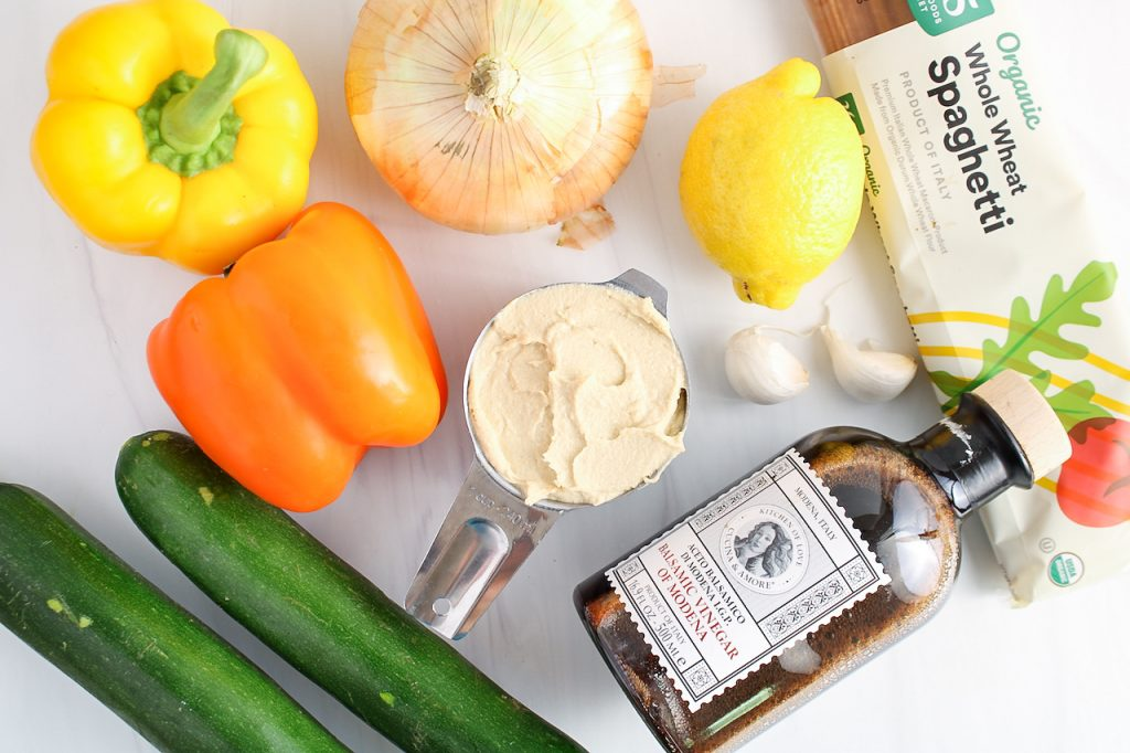 Ingredients needed to make this recipe: creamy chickpea dip zucchini, red and yellow peppers, sweet onion, garlic, lemon, balsamic vinegar and whole wheat spaghetti.
