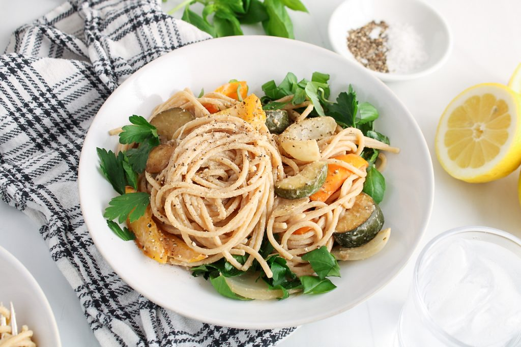 Showing is a white bowl that contains pasta with hummus and roasted vegetables. There are fresh herbs topping the pasta dish. On the side of the bowl, there are sliced lemon, salt and pepper in a small bowl, a glass of water, fresh basil and a black and white hand towel.