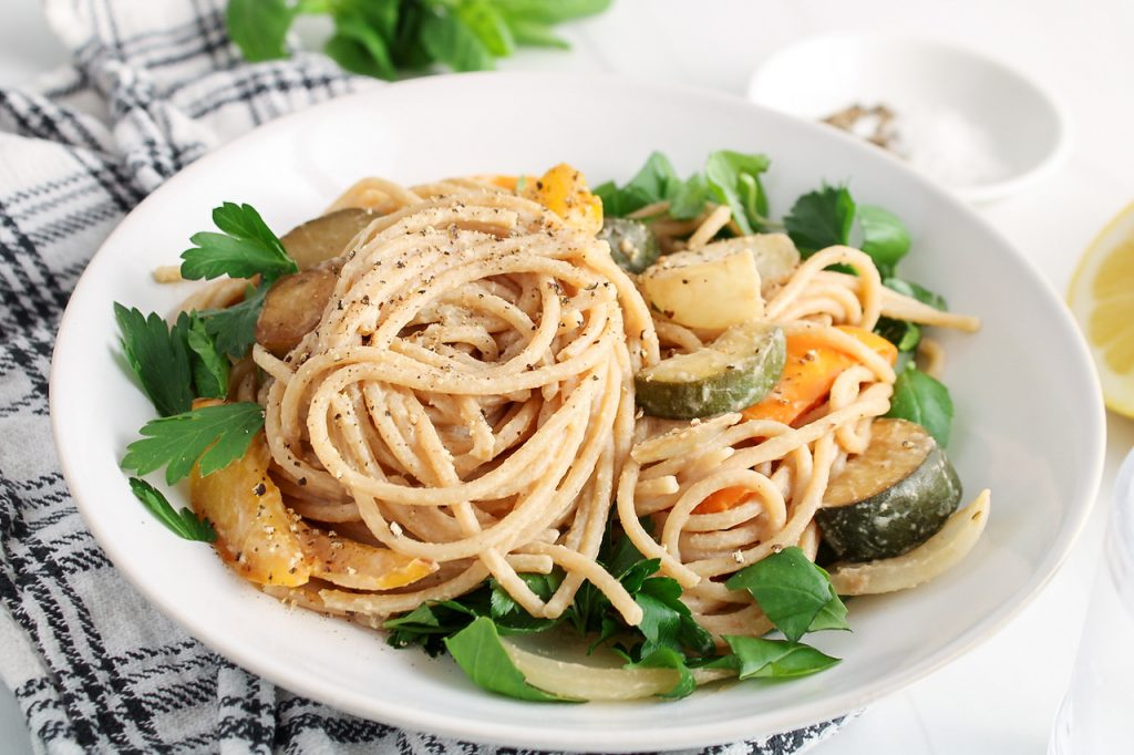 Showing is a white bowl that contains pasta with hummus and roasted vegetables. There are fresh herbs topping the pasta dish. The bowl is on a black and white hand towel.